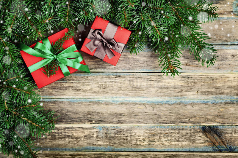 Christmas background with gift box and fir branch on wooden rustic board, festive snow effect, Christmas frame stock photography