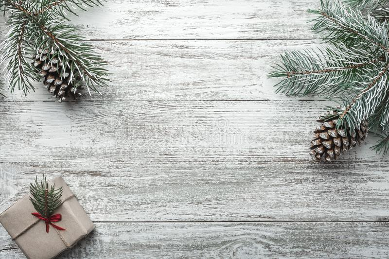 Christmas background with gift box and fir branches on old wooden table. Holidays background. royalty free stock image