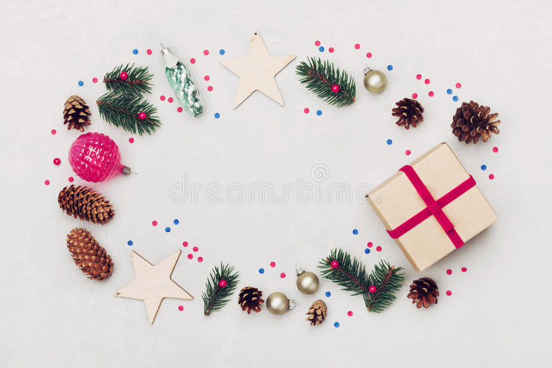 Christmas background of gift box, fir tree, conifer cone and holiday decorations on white table top view. Flat lay styling. stock images