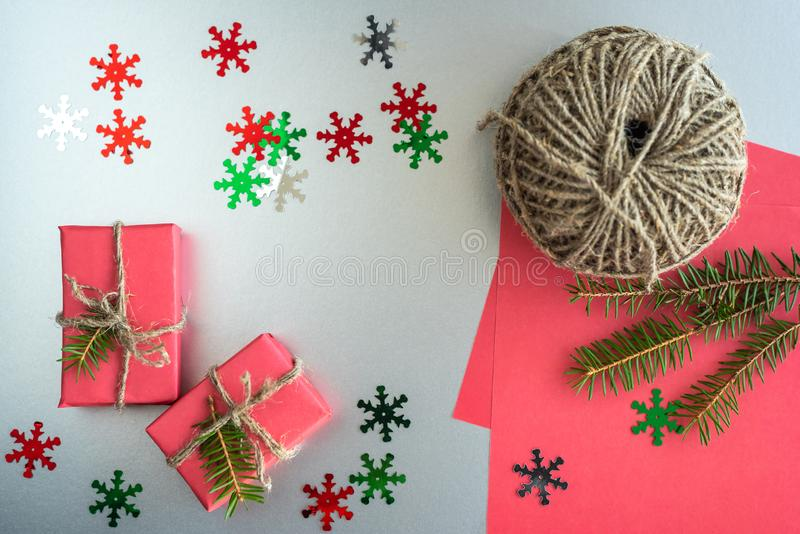 Christmas background with gift boxes, clews of rope, paper and decorations on red. Preparation for holidays. Gift wrapping concept. Top view with copy space royalty free stock photos