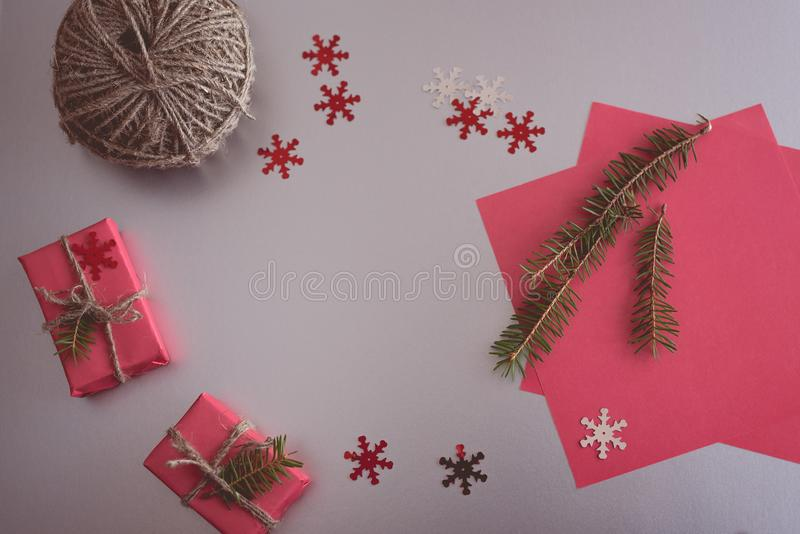 Christmas background with gift boxes, clews of rope, paper and decorations on red. Preparation for holidays. Gift wrapping concept. Top view with copy space royalty free stock photography