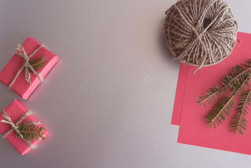 Christmas background with gift boxes, clews of rope, paper and decorations on red. Preparation for holidays. Gift wrapping concept. Top view with copy space stock photo
