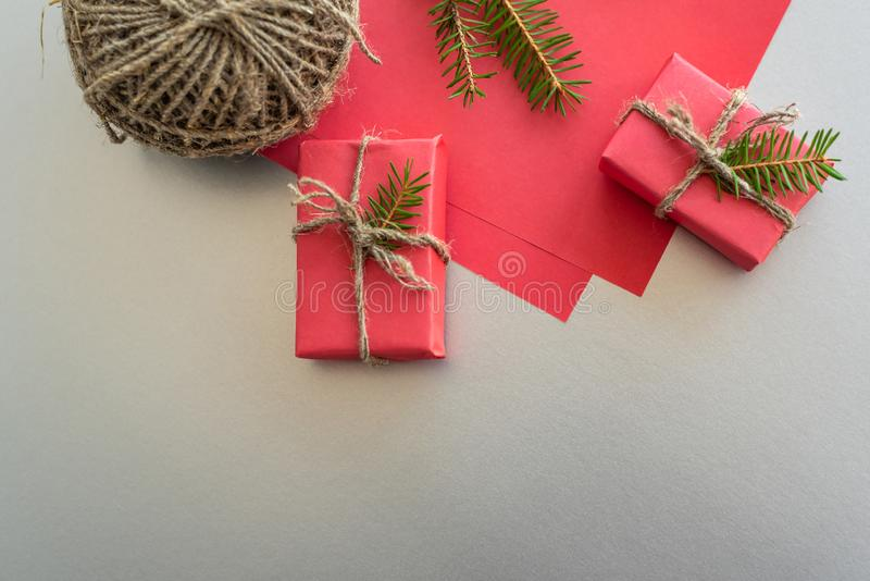Christmas background with gift boxes, clews of rope, paper and decorations on red. Preparation for holidays. Gift wrapping concept. Top view with copy space royalty free stock image