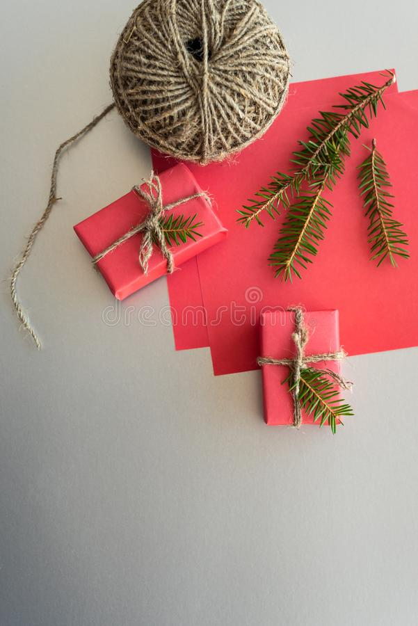 Christmas background with gift boxes, clews of rope, paper and decorations on red. Gift wrapping concept. Top view. Christmas background with gift boxes, clews stock photos