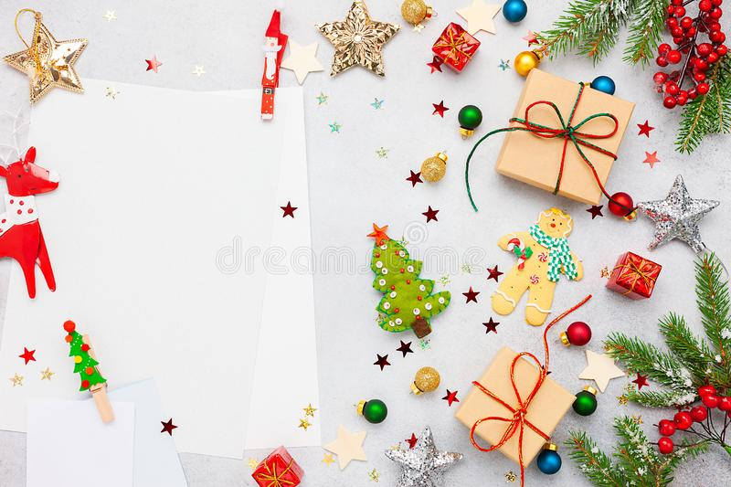Christmas background with gift boxes, festive decor, fir tree branches and paper cards notes. Flat lay royalty free stock images
