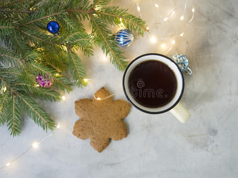 Christmas background with Gingerbread cookies, cup of tea. Cozy evening, Christmas decorations, colored balls and lights garlands. New Year card. Copy space stock image