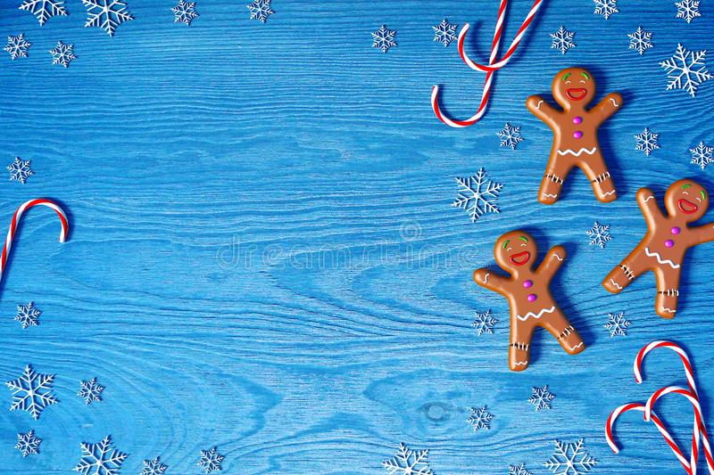 Christmas background. Gingerbread man, Christmas candy cane and snowflakes on blue wooden background with copy space for text. stock photo