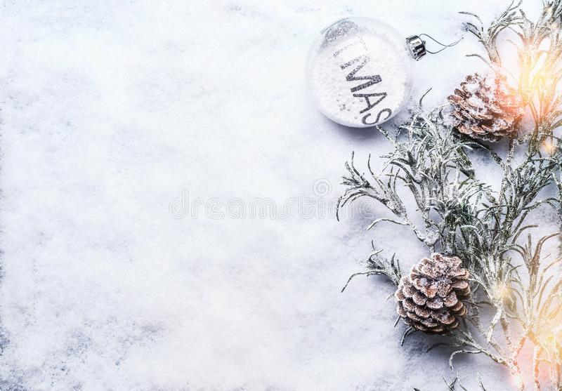 Christmas background with glass bauble , frozen branches and cones on snow with snowfall and bokeh. Top view with copy space for your design, frame stock images