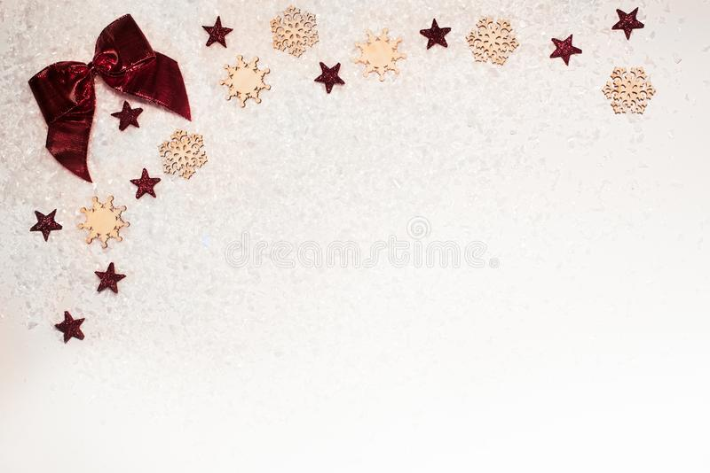 Christmas background, with glitter stars, red bow, timber snowflakes and snow - sophisticated, luxury - copyspace royalty free stock photography