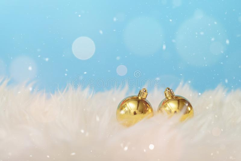 Christmas background with a gold ornament in warm white blanket. Merry christmas and happy new year greeting card with copy-space. Christmas celebration royalty free stock image
