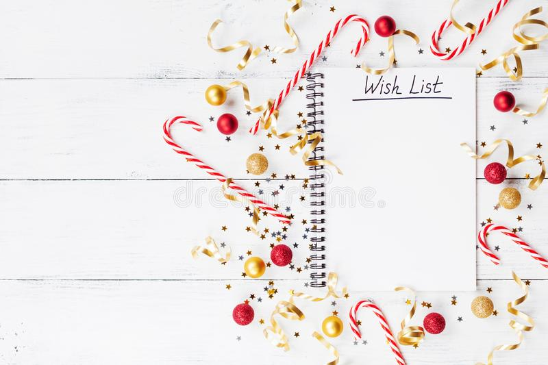 Christmas background of golden confetti, holiday decorations and wish list notebook. Top view and flat lay. Style royalty free stock image