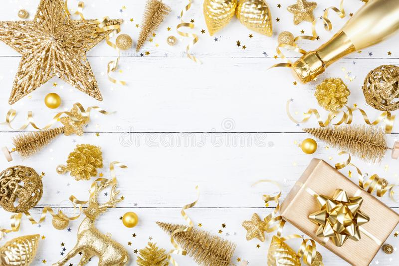 Christmas background with golden gift or present box, champagne and holiday decorations top view. Greeting card. Flat lay. Christmas background with golden gift stock images