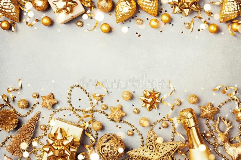 Christmas background with golden gift or present box, champagne and holiday decorations top view. Greeting card. Flat lay style stock images