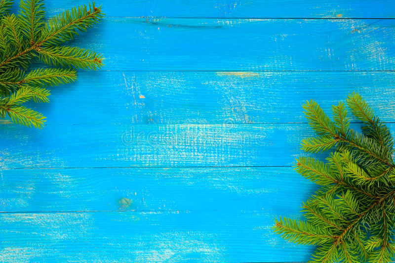 Christmas background. Green fir branches on a blue sapphire wooden table. stock photos