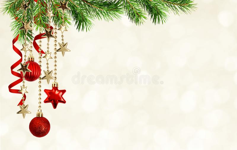 Christmas background with green pine twigs, hanging red decorations and silk twisted ribbons stock photography