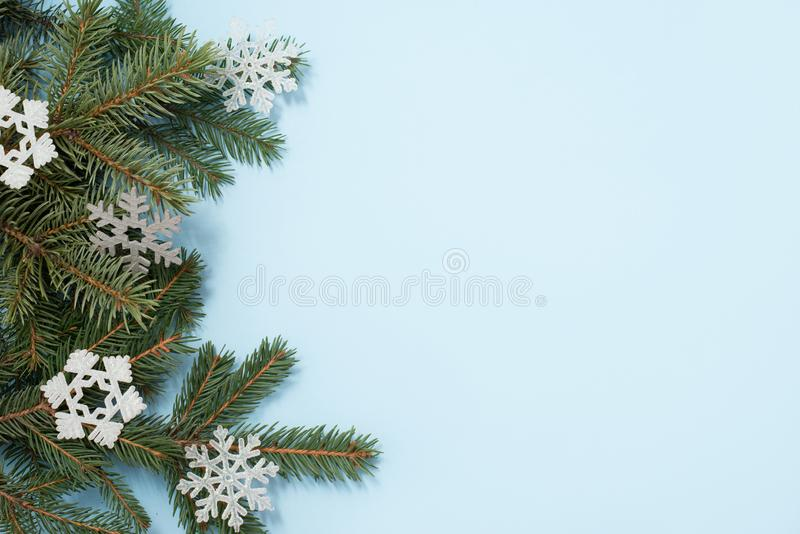 Christmas background. green tree and snowflakes decorations on blue background. Top view with copy space royalty free stock photography