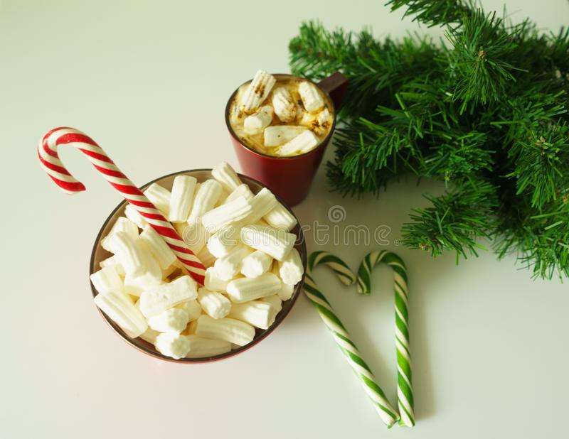 Christmas background, greeting card with a Cup of coffee or chocolate with marshmallows,candy canes, a red plate and tree branches stock illustration