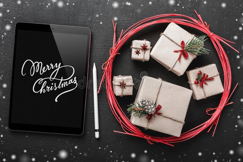 Christmas background, handmade gifts in a red circle, Merry Christmas tablet, snowflake effect. royalty free stock image