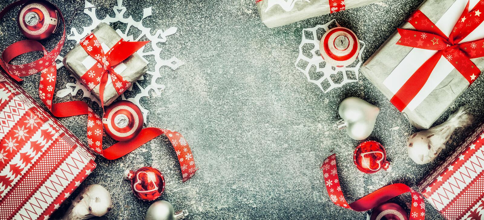 Christmas background with handmade paper snowflakes, gift boxes and red decorations on rustic background, top view. Banner stock photo