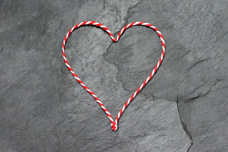 Christmas background with heart shape made of Christmas twine. On black slate stock images