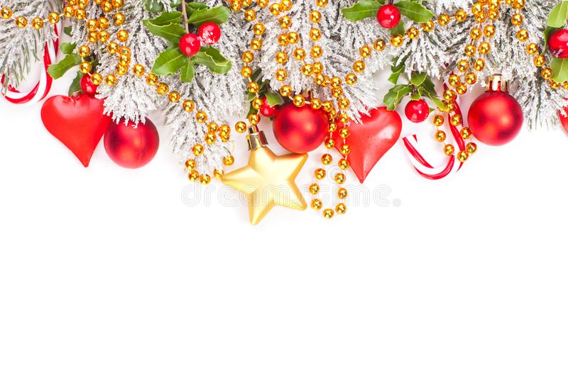 Christmas background with holly berry, red baubles, gold garland and green Xmas tree twig isolated on white. Colorful Xmas border.  stock photo