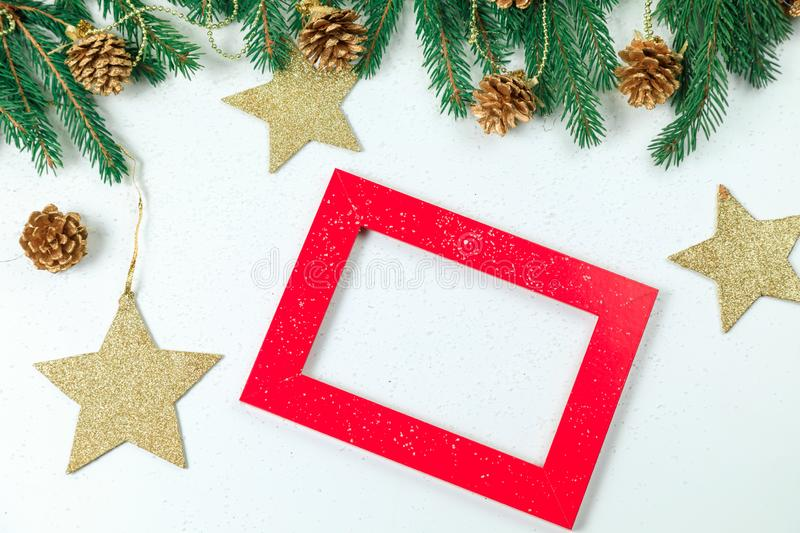 Christmas background. Christmas jewelry on fir-tree branches, gold spheres, garlands and a red frame for a photo or an inscriptio stock image