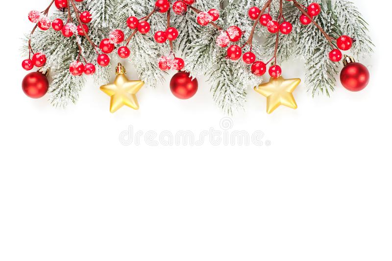 Christmas background made with evergreen tree branches, red holly berries, gold and red baubles isolated on white background. Flat lay, copy space. New Year or stock photos