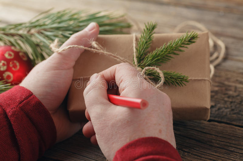 Christmas background. male hands holding New Year present. Packed gifts and scrolls, Workplace for preparing handmade decorations. stock image