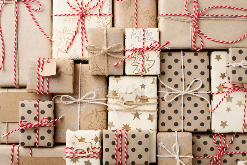 Christmas background with gift boxes wrapped in brown kraft paper flat lay. Christmas background with many decorative homemade gift boxes wrapped in brown kraft stock images