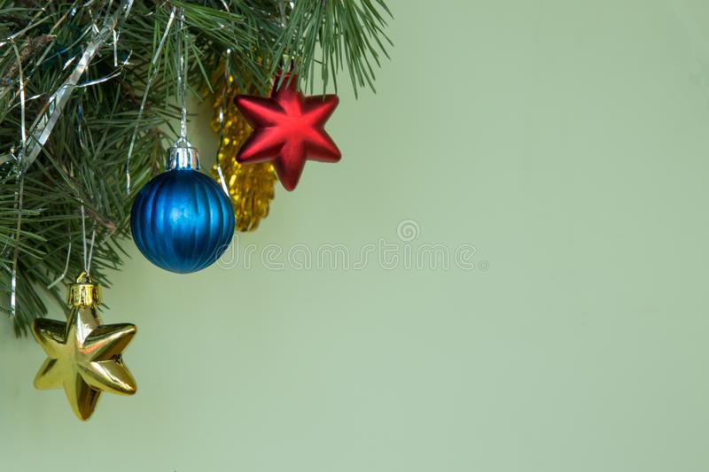 Christmas background. Natural pine branches on a green background ith blue ball and yellow red stars. Christmas background. Decoration of natural pine branches stock images