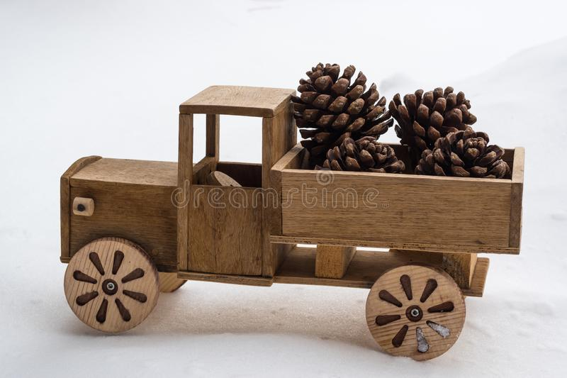 Christmas background. An old wooden toy truck carries pine cones in white snow. stock photos