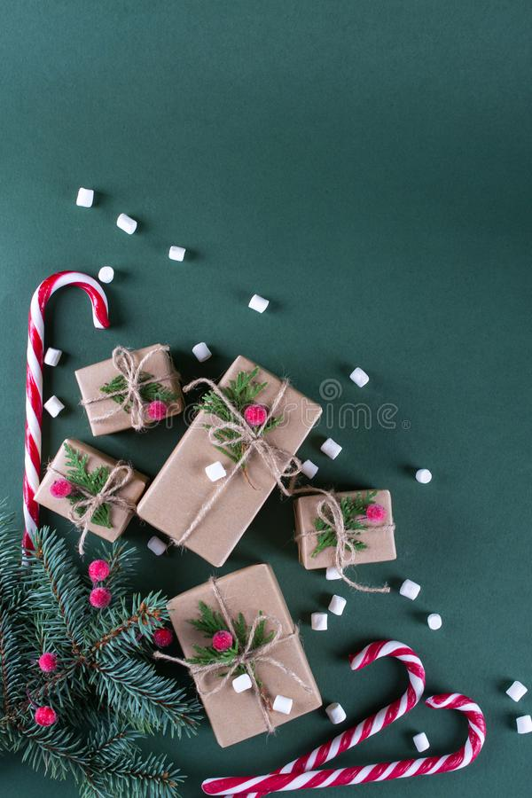 Christmas background. Packing gifts in vintage beige craft paper and natural decor. Branches of fir and red berry . Top view flat lay stock photography