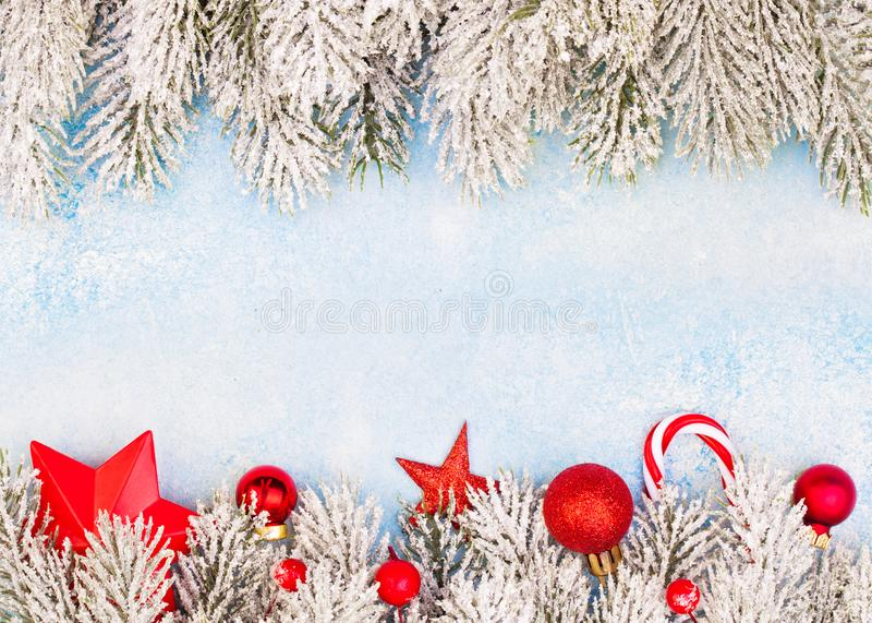 Christmas background. Perfect winter border with green Xmas tree twig and red New Year decoration on blue frozen background.  stock image