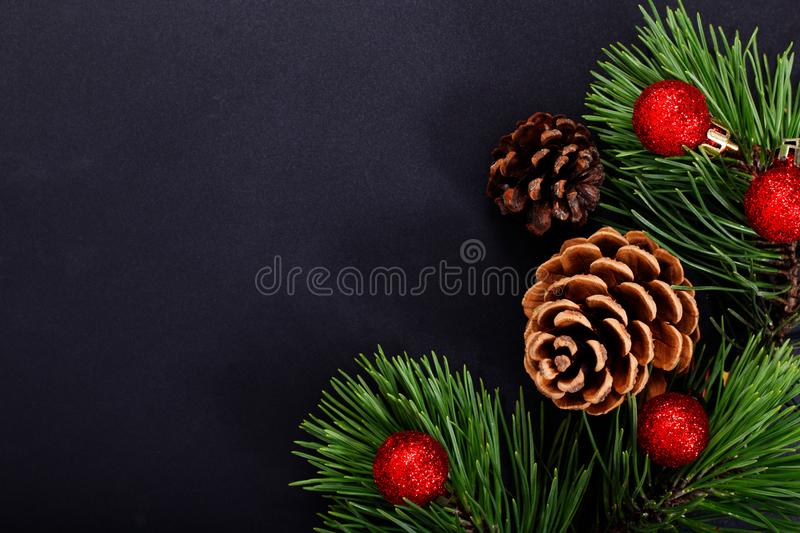 Christmas background pine leaves, pine corn and glitter ball on black background stock photography