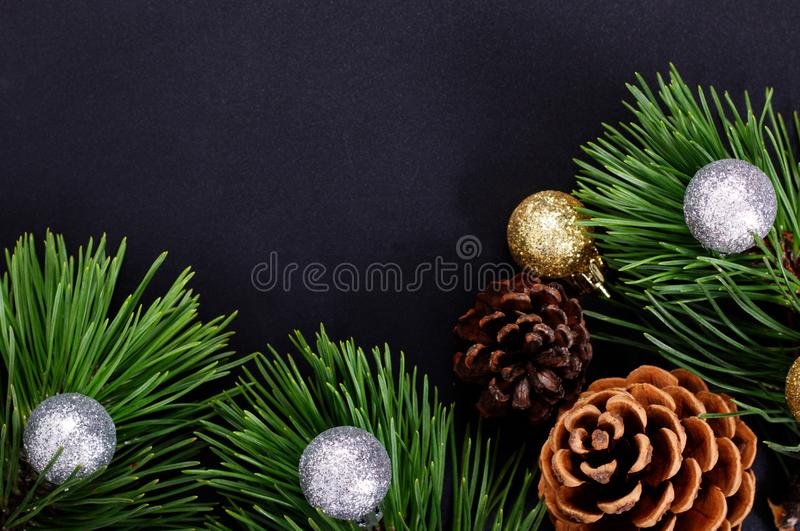 Christmas background pine leaves, pine corn and glitter ball on black background royalty free stock photos