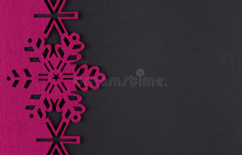 Christmas background with pink snowflakes and copy space on dark grey background stock images