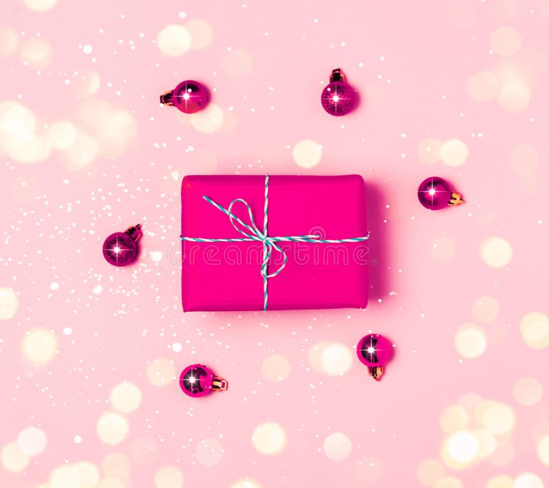 Christmas background with purple balls and present gift box and decoration on pink background stock images
