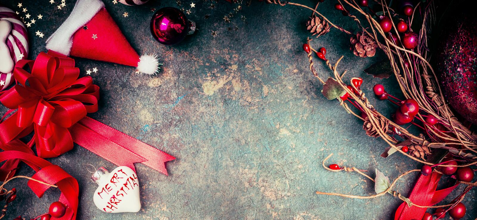 Christmas background with red holiday decoration, Merry Christmas heart, berries wreath and Santa hat, top view, banner stock photo