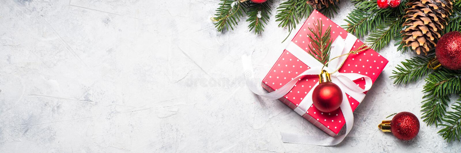 Red christmas present box, fir tree branch and decorations. stock image