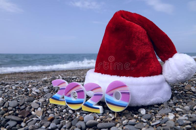 Christmas background. Red Santa hat and numbers 2020 on the background of the beach and the blue sea. stock photography