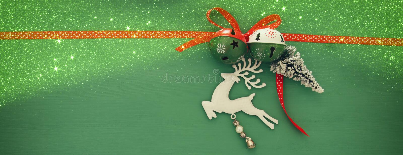 Christmas background with red silk traditional ribbon, white deer, evergreen tree and jingle bells. Christmas background with red silk traditional ribbon, white royalty free stock image
