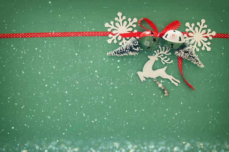 Christmas background with red silk traditional ribbon, white deer, evergreen tree, paper snowflakes and jingle bells. Christmas background with red silk royalty free stock images