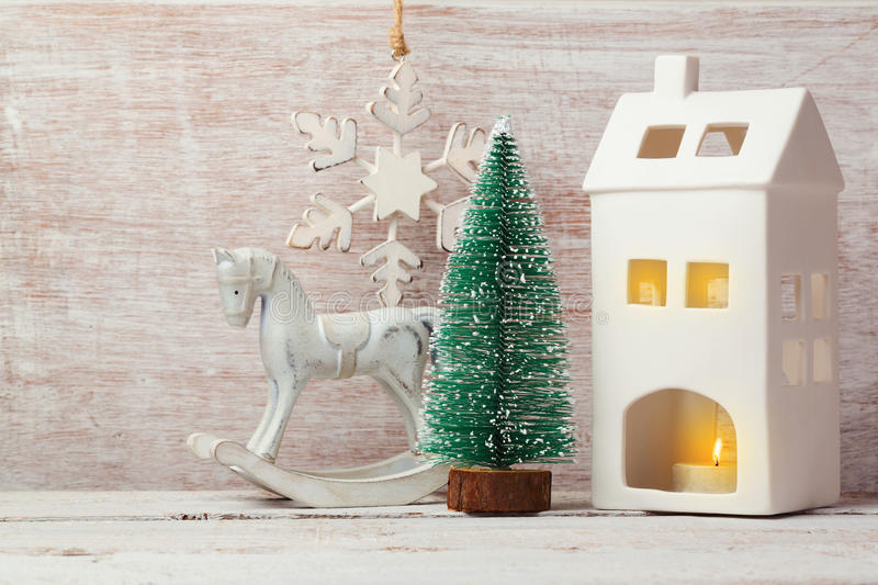 Christmas background with rustic decorations, house candle, pine tree and rocking horse royalty free stock image
