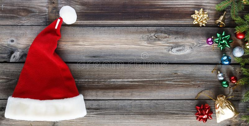 Christmas background, Santa Claus hat, Christmas decorations, wooden background. flat lay, copy space. top view. royalty free stock photography