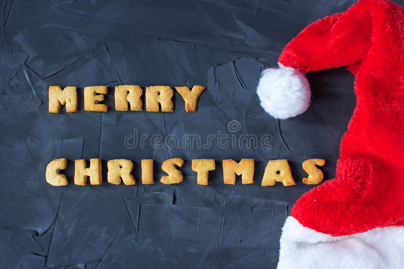 Christmas background with Santa's cap and baked gingerbread words merry christmas . creative idea. Christmas background with Santa's cap and baked gingerbread royalty free stock photos