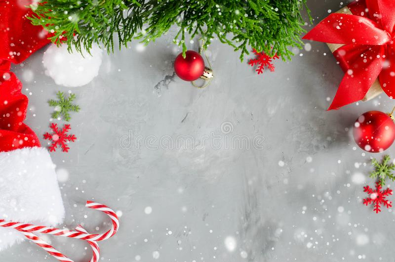 Christmas background. Santa`s cap and xmas decorations. Christmas background. Santa`s cap, red christmas present box, cup of hot tea, fir tree branch and royalty free stock photo