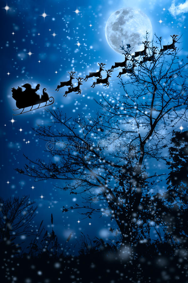 Christmas background. Silhouette of Santa Claus flying on a sleigh pulled by reindeer. Christmas background. Beautiful winter background of snowy night sky royalty free stock photo