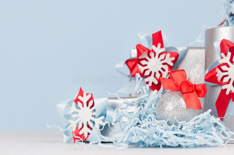 Christmas background - silver glittering ball with red silk bow closeup, blur and decorations on soft light blue color backdrop. royalty free stock photography