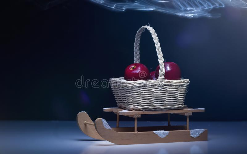 Christmas background with sled, basket with red apples, light effects, dark background stock photography