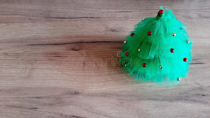 Christmas background. A small Christmas tree  on a wooden table. Green background. Space for text. New Year`s background. stock photo